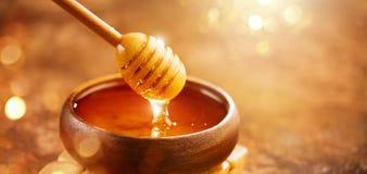Μέλι Υγιές οργανικό παχύ μέλι που στάζει από dipper μελιού στο ξύλινο κύπελλο γλυκό επιδορπίων Στοκ Εικόνες