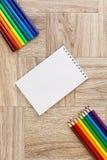 Μέρη των ανάμεικτων στυλών και των μολυβιών δεικτών χρωμάτων με το σημειωματάριο στοκ φωτογραφίες