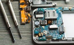 Μέρη των αποσυντεθειμένων συσκευών με τους οδηγούς βιδών στον ξύλινο πίνακα στοκ φωτογραφία με δικαίωμα ελεύθερης χρήσης