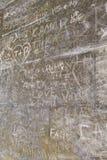 Μέρη των αρχικών ετικέττες γλυπτικών συμβόλων στον παλαιό τοίχο Στοκ Εικόνα