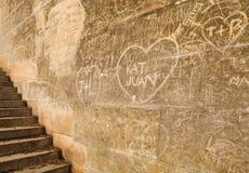 Μέρη των αρχικών ετικέττες γλυπτικών συμβόλων στον παλαιό τοίχο Στοκ Φωτογραφίες