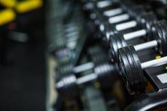 Μέρη των αλτήρων μετάλλων, βαρύς εξοπλισμός για το μέγεθος και τη δύναμη μυών σε ένα σκοτεινό θολωμένο υπόβαθρο Στοκ Φωτογραφίες
