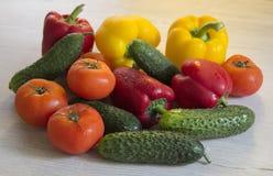 Μέρη των εύγευστων και ζωηρόχρωμων λαχανικών στον πίνακα κουζινών Στοκ Εικόνες