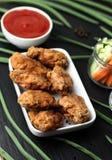 Μέρη των φτερών κοτόπουλου στο πασπάλισμα με ψίχουλα με τη σάλτσα ντοματών στο πιάτο μαύρου σχιστόλιθου Στοκ Εικόνες