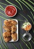 Μέρη των φτερών κοτόπουλου στο πασπάλισμα με ψίχουλα με τη σάλτσα ντοματών στο πιάτο μαύρου σχιστόλιθου Τοπ όψη Στοκ εικόνα με δικαίωμα ελεύθερης χρήσης