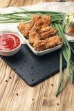Μέρη των φτερών κοτόπουλου στο πασπάλισμα με ψίχουλα με τη σάλτσα ντοματών στον καφετή ξύλινο πίνακα Στοκ Φωτογραφίες