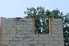 Μέρος ενός ατελούς σπιτιού με έναν γκρίζο τοίχο τούβλου και ένα παράθυρο ενάντια στον ουρανό στοκ εικόνες