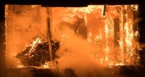 Μέρος ενός σπιτιού στην πυρκαγιά Άποψη παραθύρων στην πυρκαγιά μέσα στο ξύλινο παλαιό Χ στοκ φωτογραφία με δικαίωμα ελεύθερης χρήσης