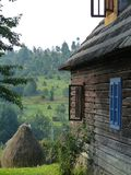 Μέρος ενός χαρακτηριστικού ξύλινου σπιτιού του Maramures στο βόρειο τμήμα της Ρουμανίας με ένα βουκολικό τοπίο στην απόσταση στοκ φωτογραφίες