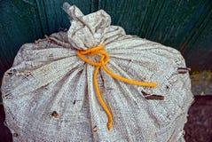 Μέρος μιας μεγάλης παλαιάς γκρίζας τσάντας που δένεται με μια πορτοκαλιά δαντέλλα στοκ φωτογραφίες