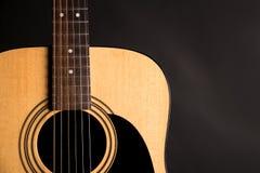 Μέρος μιας ξύλινης ακουστικής κιθάρας στη αριστερή πλευρά του πλαισίου, σε ένα απομονωμένο ο Μαύρος υπόβαθρο Στοκ Εικόνες
