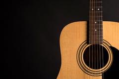 Μέρος μιας ξύλινης ακουστικής κιθάρας στη δεξιά πλευρά του πλαισίου, σε ένα απομονωμένο ο Μαύρος υπόβαθρο Στοκ εικόνες με δικαίωμα ελεύθερης χρήσης