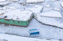 Μέρος της βάρκας και της πλαστικής καρέκλας στον παγωμένο ποταμό Δούναβης στοκ εικόνες