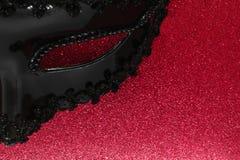 Μέρος της μαύρης μάσκας καρναβαλιού στο λάμποντας υπόβαθρο χρώματος του Μπορντώ στοκ εικόνες