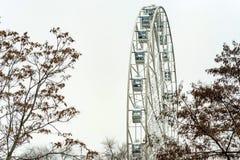 Μέρος της σύγχρονης άσπρης ρόδας Ferris και του γκρίζου ουρανού στοκ φωτογραφία