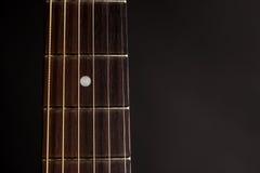 Μέρος του λαιμού, ξύλινη ακουστική κιθάρα, στη αριστερή πλευρά του πλαισίου, σε ένα μαύρο υπόβαθρο Στοκ Εικόνες