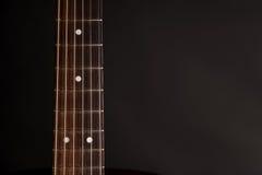 Μέρος του λαιμού, ξύλινη ακουστική κιθάρα, στη αριστερή πλευρά του πλαισίου, σε ένα απομονωμένο ο Μαύρος υπόβαθρο Στοκ φωτογραφία με δικαίωμα ελεύθερης χρήσης