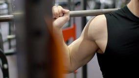 Μέρος του αρσενικού κορμού, ο οποίος crouches με το barbell στους ώμους στη γυμναστική φιλμ μικρού μήκους