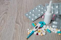 Μέρος του ζωηρόχρωμων φαρμάκου και των χαπιών άνωθεν στο γκρίζο ξύλινο υπόβαθρο Όλοι για τη γρίπη - ρινικός ψεκασμός, βιταμίνες,  Στοκ φωτογραφία με δικαίωμα ελεύθερης χρήσης