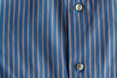 Μέρος του μπλε ριγωτού πουκάμισου με τη σύσταση ή το υπόβαθρο κουμπιών Στοκ Φωτογραφίες