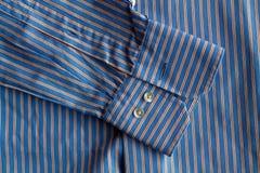 Μέρος του μπλε ριγωτού πουκάμισου με τη σύσταση ή το υπόβαθρο κουμπιών Στοκ Φωτογραφία