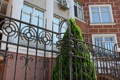 Μέρος του φράκτη των μαύρων αιχμηρών ράβδων σιδήρου κοντά στις πράσινες ερυθρελάτες και του τοίχου του σπιτιού με ένα παράθυρο στοκ εικόνες
