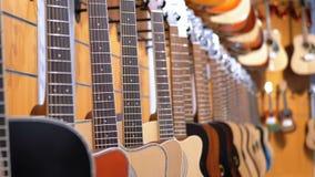 Μέρος των ακουστικών κιθάρων που κρεμούν σε ένα κατάστημα μουσικής Μουσικά όργανα καταστημάτων απόθεμα βίντεο