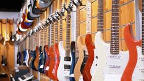 Μέρος των ηλεκτρικών κιθάρων που κρεμούν σε ένα κατάστημα μουσικής Μουσικά όργανα καταστημάτων φιλμ μικρού μήκους