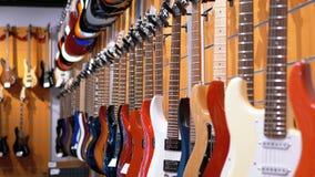 Μέρος των ηλεκτρικών κιθάρων που κρεμούν σε ένα κατάστημα μουσικής Μουσικά όργανα καταστημάτων απόθεμα βίντεο