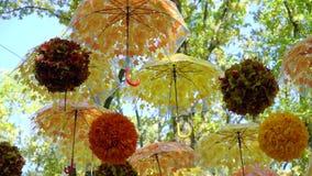 Μέρος των λαμπρά πορτοκαλιών και κίτρινων ομπρελών και των σφαιρών που κρεμούν και που κινούνται στον αέρα στο πάρκο φθινοπώρου απόθεμα βίντεο