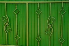Μέρος των πράσινων πορτών με τις σφυρηλατημένες ράβδους και το όμορφο σχέδιο Στοκ Φωτογραφίες