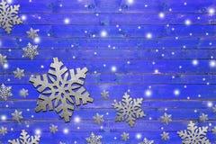 Μέρος snowflake σιδήρου στον ξεπερασμένο μπλε ξύλινο πίνακα Στοκ Φωτογραφία