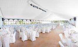 Μέσα σε μια μεγάλη οργάνωση γαμήλιων σκηνών για μια υποδοχή με τις σειρές των πινάκων Στοκ Φωτογραφίες