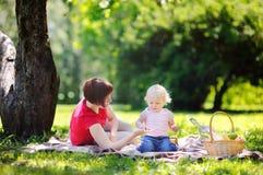 Μέσες ηλικίας γυναίκα και αυτή λίγος εγγονός που έχει ένα πικ-νίκ Στοκ Εικόνα