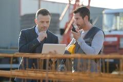 Μέσης ηλικίας άνδρας εργαζόμενος που χρησιμοποιεί walkie-talkie με το συνάδελφο στοκ φωτογραφίες