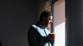 Μέσης ηλικίας άτομο που ρουφά γουλιά γουλιά το καυτό φλυτζάνι καφέ δίπλα στο παράθυρο απόθεμα βίντεο