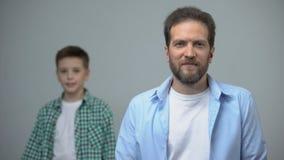 Μέσης ηλικίας άτομο που χαμογελά στο μικρό παιδί καμερών που στέκεται πίσω, μνήμες παιδικής ηλικίας απόθεμα βίντεο