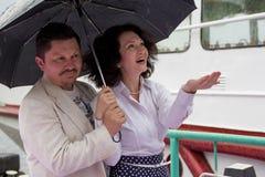 Μέσης ηλικίας ανδρών γυναικών βροχής ομπρελών αισθησιακή αμοιβή αγάπης ζευγών αληθινή στοκ φωτογραφία με δικαίωμα ελεύθερης χρήσης