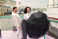 Μέσης ηλικίας ανδρών γυναικών βροχής ομπρελών αισθησιακή αμοιβή αγάπης ζευγών αληθινή στοκ φωτογραφία