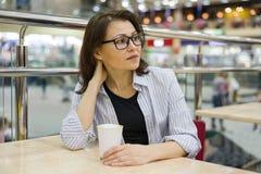 Μέσης ηλικίας γυναίκα σε έναν πίνακα με το φλιτζάνι του καφέ, ψωνίζοντας κέντρο ψυχαγωγίας υποβάθρου Στοκ εικόνες με δικαίωμα ελεύθερης χρήσης