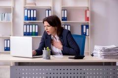 Μέσης ηλικίας γυναίκα υπάλληλος που υποφέρει στο γραφείο στοκ εικόνα