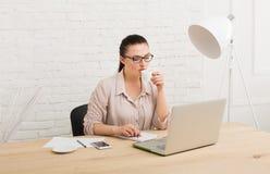 Μέσης ηλικίας επιχειρησιακή γυναίκα στην αρχή με τον καφέ Στοκ εικόνες με δικαίωμα ελεύθερης χρήσης