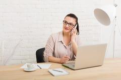 Μέσης ηλικίας επιχειρησιακή γυναίκα στην αρχή με το τηλέφωνο Στοκ Εικόνες