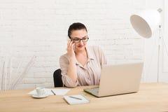 Μέσης ηλικίας επιχειρησιακή γυναίκα στην αρχή με το τηλέφωνο Στοκ Φωτογραφίες