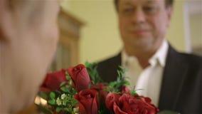 Μέσης ηλικίας άνδρας που δίνει την ανθοδέσμη γυναικών των κόκκινων τριαντάφυλλων απόθεμα βίντεο
