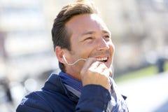 Μέσης ηλικίας άτομο με τα ακουστικά που μιλούν στο τηλέφωνο Στοκ εικόνες με δικαίωμα ελεύθερης χρήσης