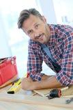 Μέσης ηλικίας άτομο με τα εργαλεία που λειτουργούν στην εγχώρια βελτίωση στοκ φωτογραφία με δικαίωμα ελεύθερης χρήσης