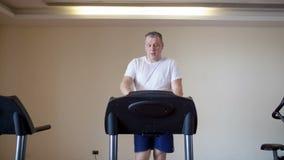 Μέσης ηλικίας άτομο που επιλύει treadmill απόθεμα βίντεο