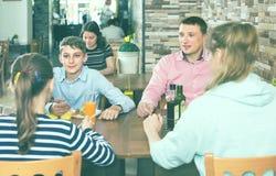 Μέσης ηλικίας γονείς και παιδιά που κουβεντιάζουν κατά τη διάρκεια του γεύματος στο famil Στοκ εικόνα με δικαίωμα ελεύθερης χρήσης