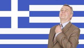 Μέσης ηλικίας γραβάτα ρύθμισης επιχειρηματιών με την υπερηφάνεια πέρα από την ελληνική σημαία Στοκ φωτογραφία με δικαίωμα ελεύθερης χρήσης